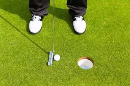 Joueur de golf mettant balle dans le trou, seulement les pieds de fer et d'être vu Banque d'images