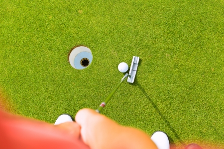 cropped shots: Golf player putting ball into hole, only feet and iron to be seen