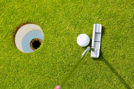 cropped shots: Golf player putting ball into hole, only ball, hole and iron to be seen