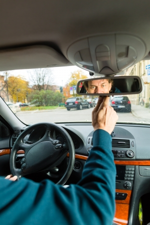 rear view mirror: Experienced taxi driver is looking in the rear view mirror in his taxi, he sets the taximeter Stock Photo