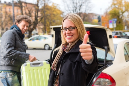Young woman standing in front of taxi, she has reached her destination, the taxi driver will help with the luggage photo