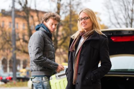 osiągnął: MÅ'oda kobieta stoi przed taksówkÄ…, że osiÄ…gnęła swój cel, taksówkarz pomoże z bagażem