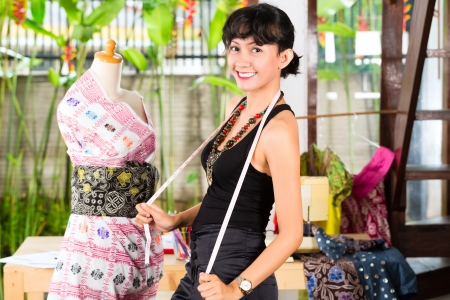 tailor: Freelancer - Fashion designer working at home on a design or draft, she takes measure on a dressmakers dummy