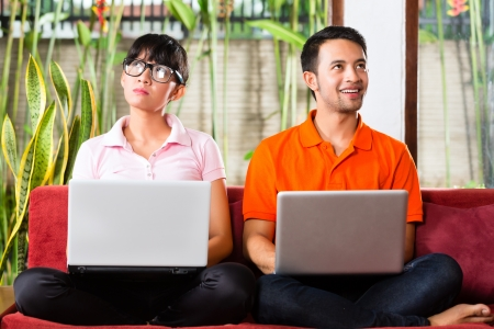 intimately: Young Indonesian couple sitting with laptops on a couch, maybe the have an idea or inspiration