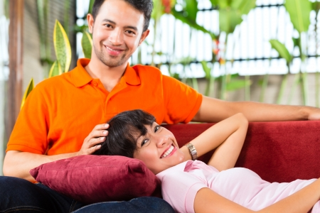 intimately: Indonesian couple sitting cozy at home on the sofa and relaxing Stock Photo