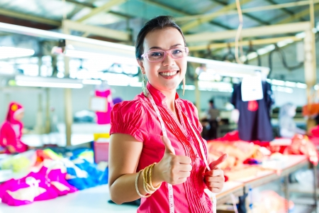 Female Chinese asian dressmaker or designer standing proudly in a textile factory, it is her workplace photo