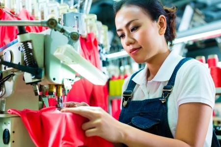 industria textil: Costurera o trabajador chino en una costura f�brica con una m�quina de coser industrial, que es muy precisa