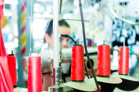 the textile industry: Spools of an industrial sewing machine in a factory, in the background working a seamstress Stock Photo