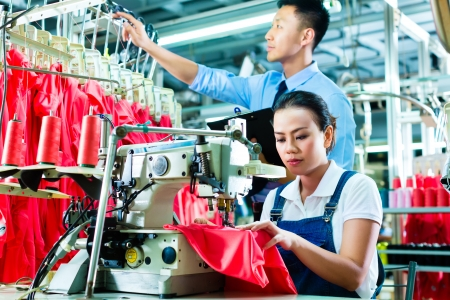 factory worker: Seamstress or worker in a factory sewing with a sewing machine, a foreman checks the yarn Stock Photo