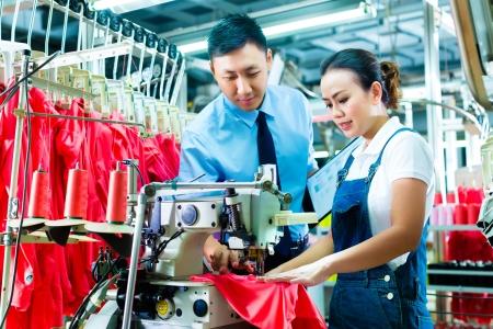 Naaister is nieuw toegewezen aan een machine in een textielfabriek, de voorman verklaart iets Stockfoto