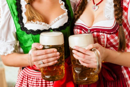 stein: Two young women in traditional Bavarian Tracht in restaurant or pub with beer and beer stein