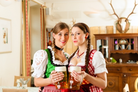 Two young women in traditional Bavarian Tracht in restaurant or pub with beer and beer stein photo