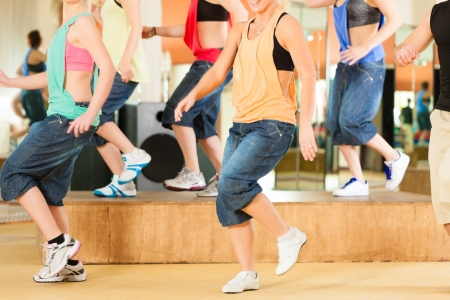dance studio: Zumba or Jazzdance - young people dancing in a studio or gym doing sports or practicing a dance number Stock Photo