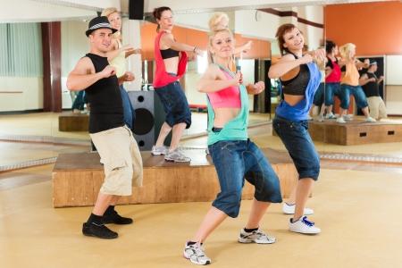 chicas bailando: Zumba o Jazzdance - gente joven que baila en un estudio o gimnasio haciendo deportes o la pr�ctica de un n�mero de baile Foto de archivo