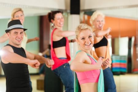 Zumba of Jazzdance - jonge mensen dansen in een studio of sportschool doen sporten of het beoefenen van een dansnummer Stockfoto