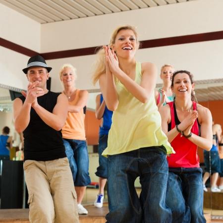 bailarin hombre: Zumba o Jazzdance - gente joven que baila en un estudio o gimnasio haciendo deportes o la pr�ctica de un n�mero de baile Foto de archivo