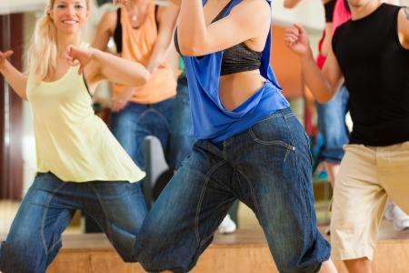 Zumba o Jazzdance - gente joven que baila en un estudio o gimnasio haciendo deportes o la práctica de un número de baile