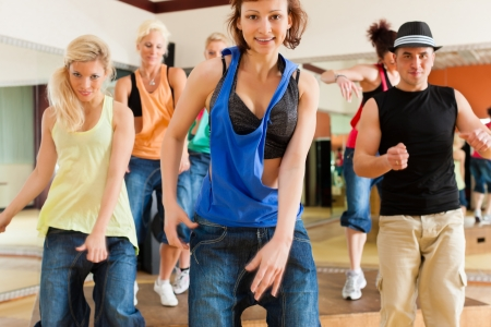 Zumba ou jazzdance - jeunes gens qui dansent dans un studio ou salle de gym faire du sport ou pratiquer un numéro de danse