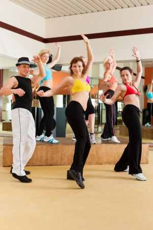 zumba: Zumba or Jazzdance - young people dancing in a studio or gym doing sports or practicing a dance number Stock Photo