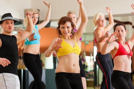 zumba: Zumba o Jazzdance - gente joven que baila en un estudio o gimnasio haciendo deportes o la práctica de un número de baile Foto de archivo