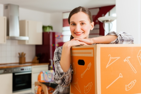 moving out: Young woman with moving box in her house moving in or out of a apartment Stock Photo