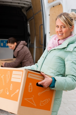 moving van: Two young women loading into a moving truck, they carry moving boxes Stock Photo