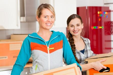 uitpakken: Jonge vrouwen - vermoedelijk vrienden - met bewegende doos in haar huis bewegen in of uit een appartement, focus op bewegende doos