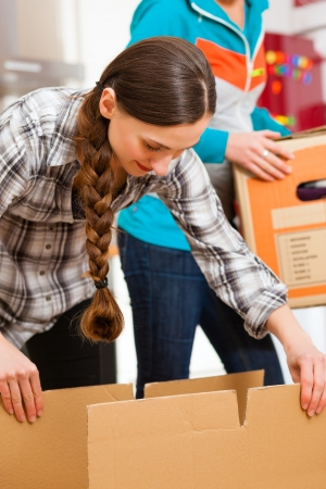shipper: Young women - presumably friends - with moving box in her house moving in or out of a apartment, focus on moving box Stock Photo