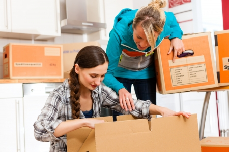 moving in: Young women - presumably friends - with moving box in her house moving in or out of a apartment, focus on moving box Stock Photo