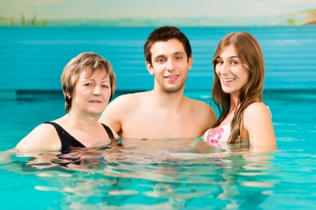 Wellness - mature woman and young couple swimming in swimming pool or doing water gymnastics, also a concept for wells of youth photo