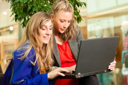 Zwei Freundinnen gehen In zusammen In Einkaufen und Haben Eine Menge Spa beim Shoppen in Einer Mall, SIE Haben Ein Laptop Gekauft Standard-Bild - 18165396