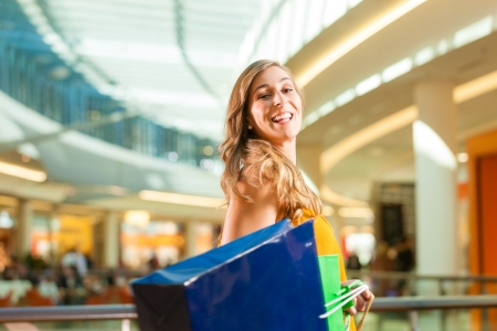 Young happy woman with shopping bags having fun while shopping in a mall Stock Photo - 18165160