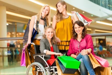 sillas de ruedas: Cuatro amigas con bolsas de la compra que se divierten mientras que las compras en un centro comercial, tiendas en el fondo, una mujer est� sentada en una silla de ruedas