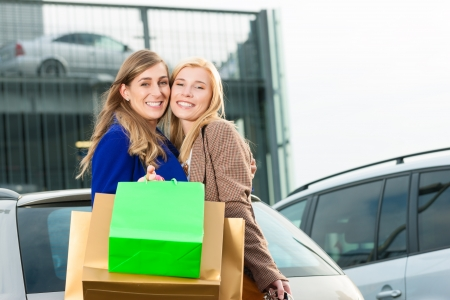 Two women were shopping in a mall or shopping centre and driving home now with their car photo