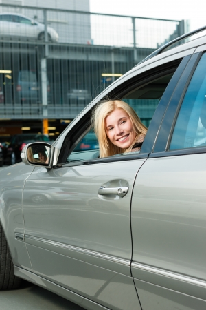 Woman back her car on a parking level or parking deck photo