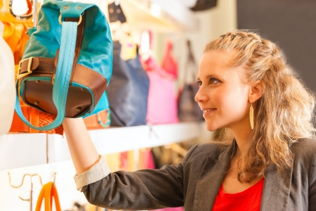 Young happy woman with shopping bags having fun while shopping in a mall Stock Photo - 18165401