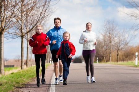 niño corriendo: Familia, madre, padre e hijos se están ejecutando o trotar al aire libre para el deporte