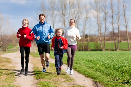 Family, mother, father and children are running or jogging for sport outdoors photo