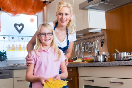domestic chore: Mother and daughter cooking together, they making Lasagna Stock Photo