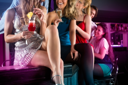 cocktail dress: Young people in club or bar drinking cocktails and having fun Stock Photo