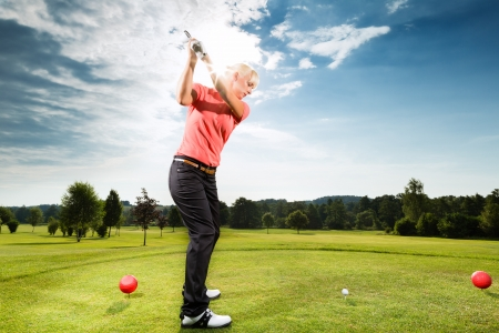 golf tee: Young female golf player on course doing golf swing, she presumably does exercise Stock Photo