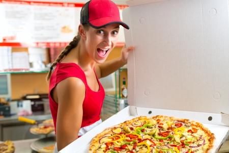 caja de pizza: Mujer que sostiene una pizza entera en la mano y le pide que pedir una pizza Foto de archivo