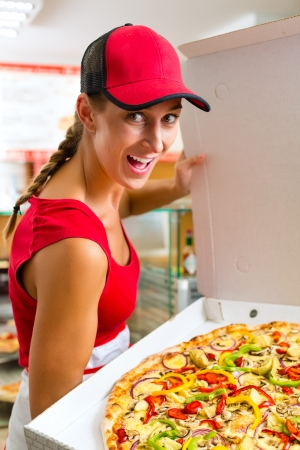 Woman holding a whole pizza in hand and asking you to ordering a pizza photo