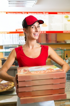 Woman holding several pizza boxes and smiling photo