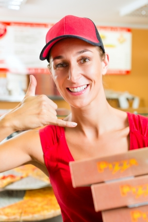Woman holding several pizza boxes in hand and asking you to order pizza for delivery photo