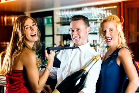 magnum: Good friends - bartender and women - with a large magnum bottle champagne at bar having fun, she pulls on his tie