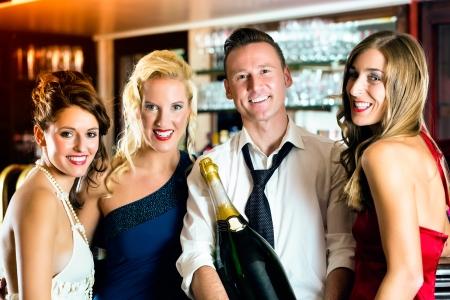 magnum: Les bons amis - barman et les femmes - avec une bouteille de champagne magnum grande au bar en s'amusant
