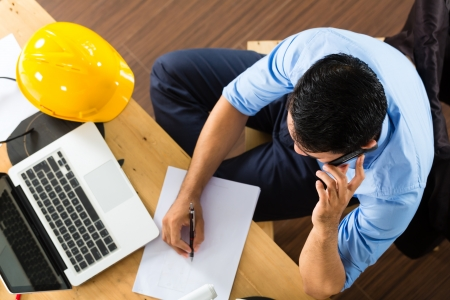 Freelancer - Architect working at home on a design or draft, on his desk are books, a laptop and a helmet or hard hat Stock Photo - 18165246