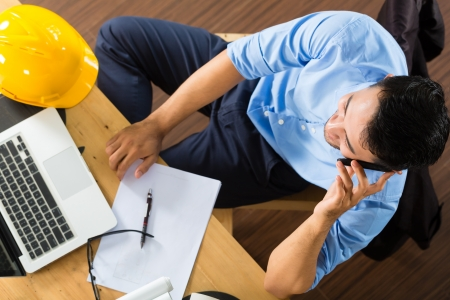 freelance: Freelancer - Architect working at home on a design or draft, on his desk are books, a laptop and a helmet or hard hat Stock Photo