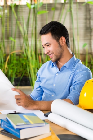 Freelancer - Architect working at home on a design or draft, on his desk are books, a laptop and a helmet or hard hat Stock Photo
